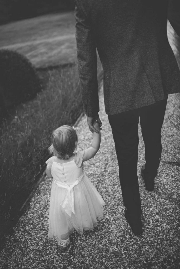 Holding flower girls hand Ashfield House Wigan Wedding Photographer by Ollie Gyte Photography